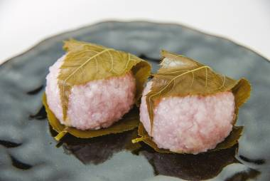 Bean paste rice cake wrapped in a cherry leaf on black dish