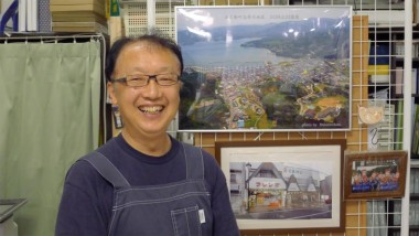 Mr. Kumagai, a local shop, keeping stands next to pictures of the town and his shop before the tsunami.