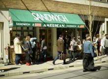 American is easily recognized by its green awning. The window right of the entry is a take-away counter.