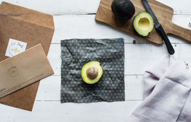 Table set up with cutting board, beeswax wrap and avocado cut in half